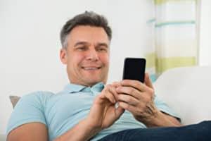 Mann lernt mittels Onlinesprachkurse mit einem Smartphone